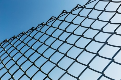 View of the blue sky through a chain link fence.
