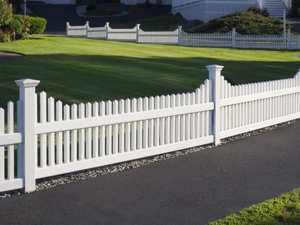 Vinyl fence surrounding a Baton Rouge yard with beautiful green grass.